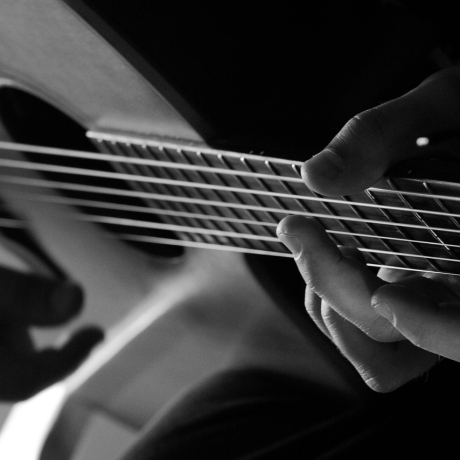 black and white photograph of musician playing guitar for Barnabas Me